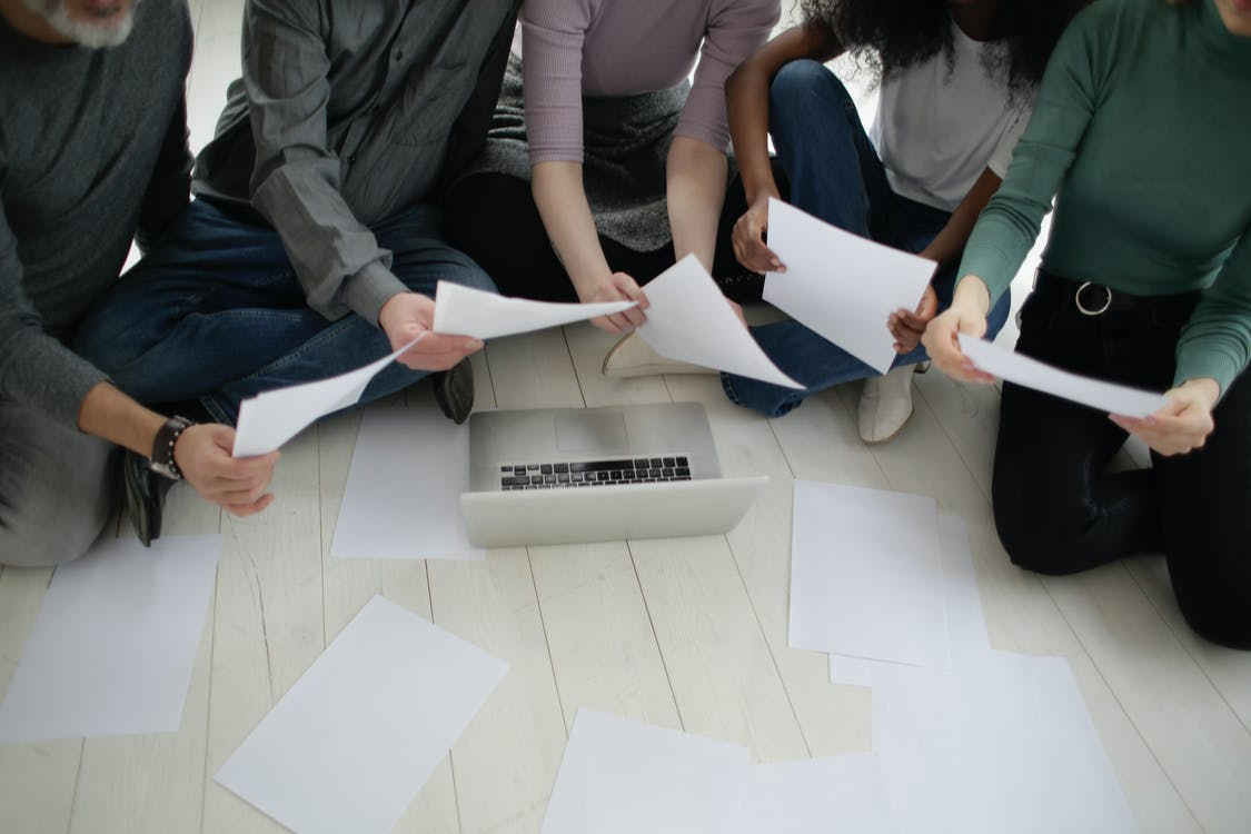 From above multiracial colleagues working with papers and laptop on floor in office