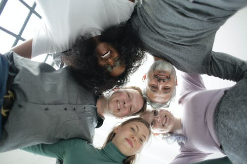 Multiethnic colleagues of different ages in casual wear standing in circle and hug each other smiling at camera in light workspace
