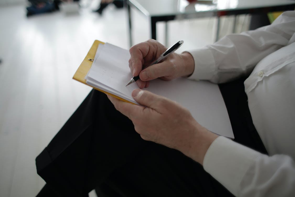 Unrecognizable businessman taking notes in documents in modern office