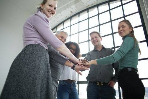 Cheerful multiethnic colleagues of different ages stacking hands together in modern office