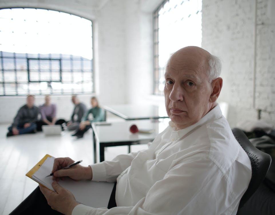 Senior male director writing strategy in modern workspace