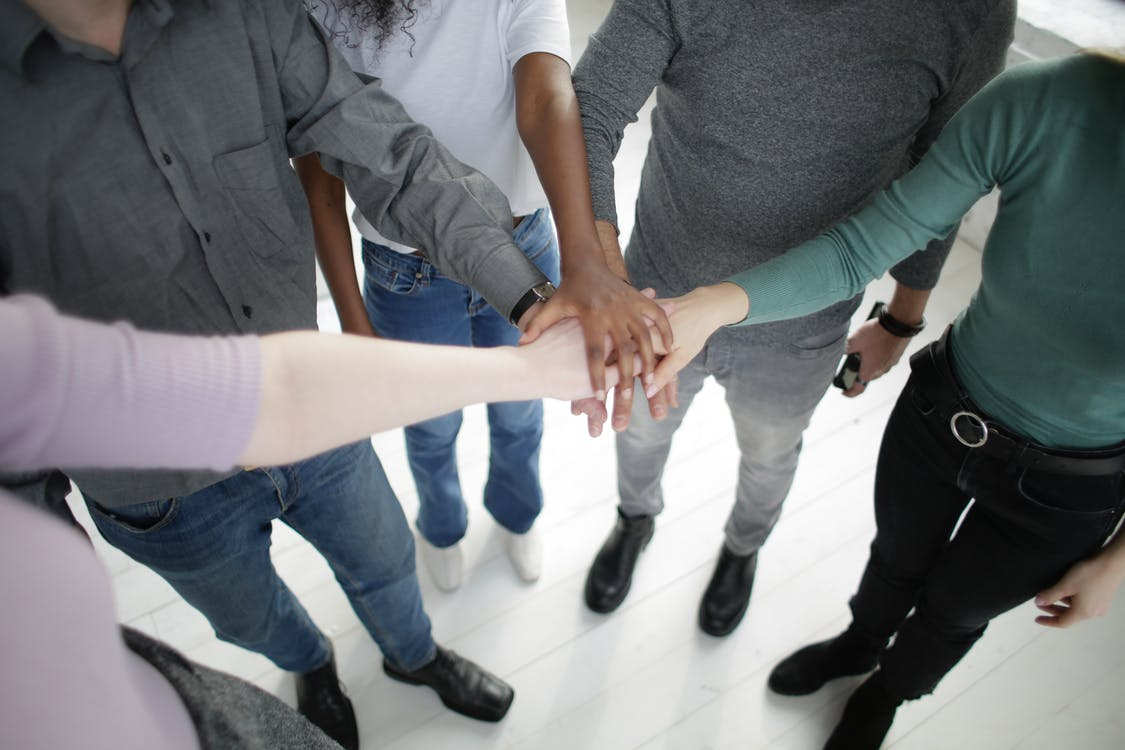 Crop multiracial people joining hands together during break in modern workplace