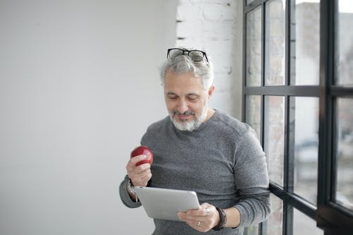 Positive mature employee surfing tablet while eating apple in light workplace