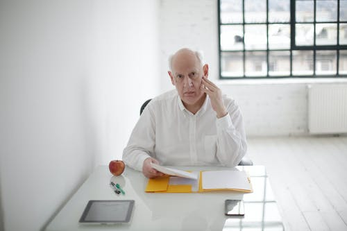 Senior male manager working with documents in modern workspace
