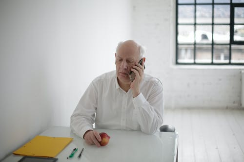 Thoughtful senior man speaking on smartphone in light office