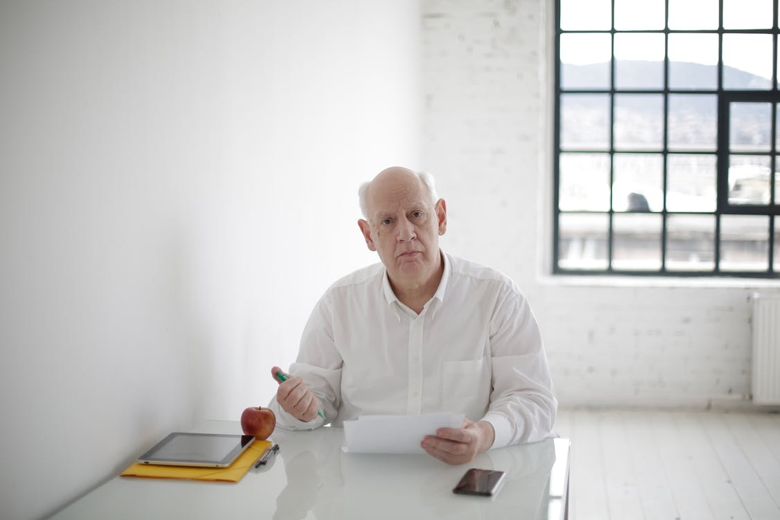 Serious elderly man writing in papers in light office