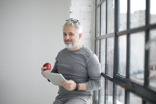 Smiling middle aged man using tablet and holding apple near window in office