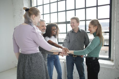 Group of smiling multiracial colleagues stacking hands together during teamwork in light office