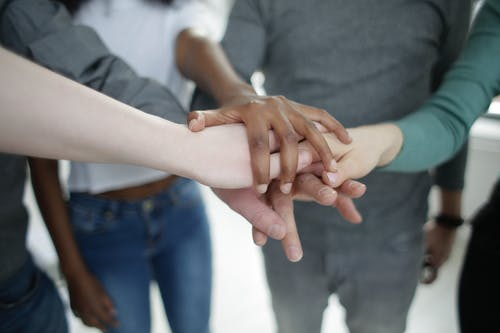 Crop diverse colleagues stacking hands together during training in office