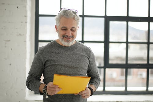 Cheerful mature male employee holding documents against window in workspace