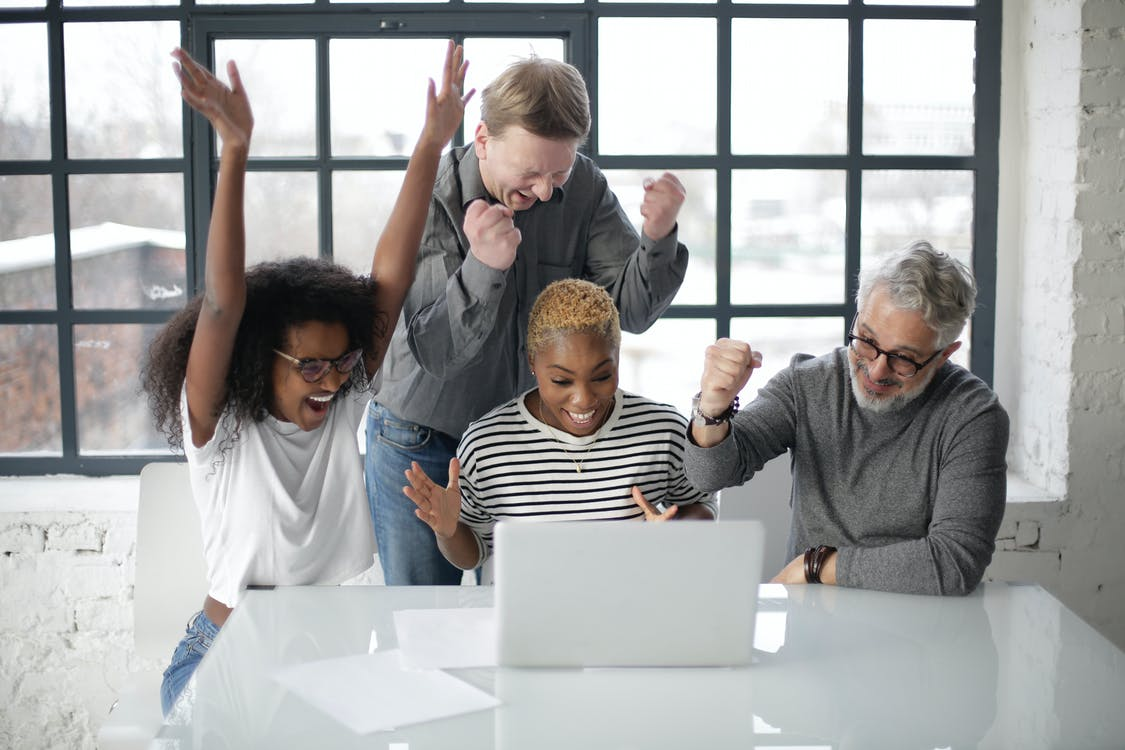 Cheerful multiethnic coworkers of different ages in casual clothing clenching fists and raising hands up in joy during successful teamwork in room