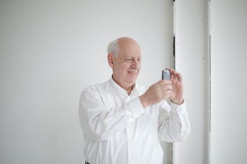 Cheerful bald man taking photo on smartphone