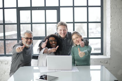 Smiling colleagues with laptop and thumbs up working in office