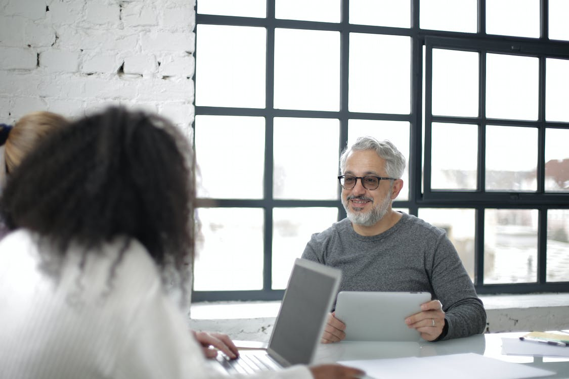 Cheerful aged gray haired man with tablet in casual clothes sitting with coworkers with laptop while working on project together