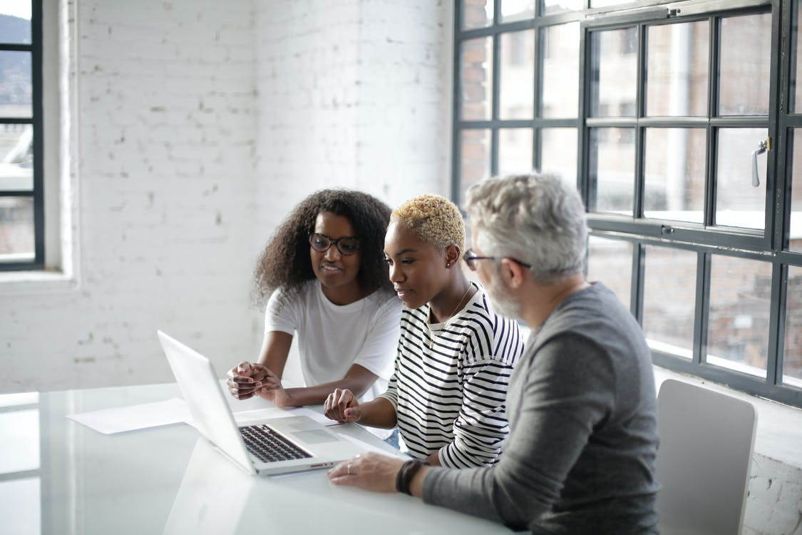 Side view of black women and old gray haired man sitting at table and surfing laptop while working on creative project