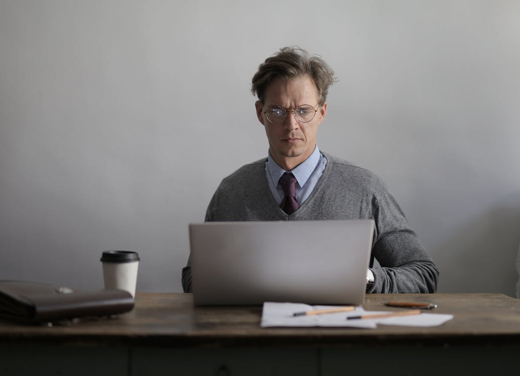 Serious focused man in formal wear and eyeglasses sitting at table with cup of coffee paper and bag while working on laptop