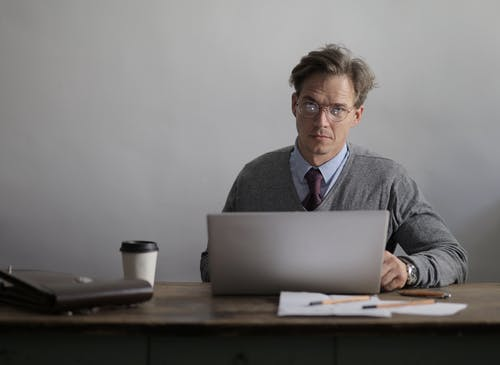 Thoughtful man with cup of coffee using laptop