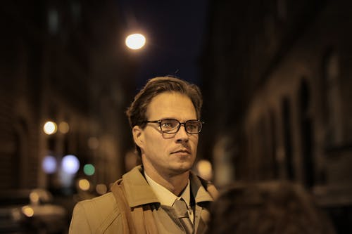 Serious man in glasses standing on street