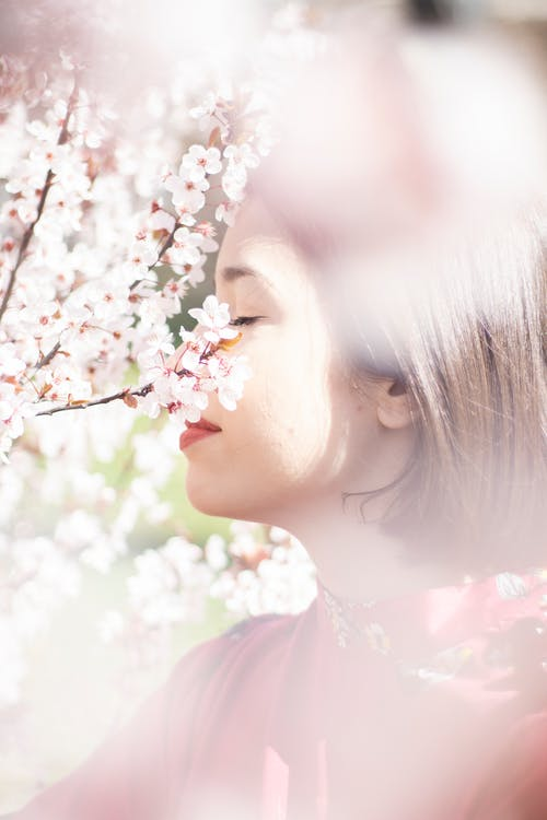 Tender young lady enjoying fresh scent of flowers
