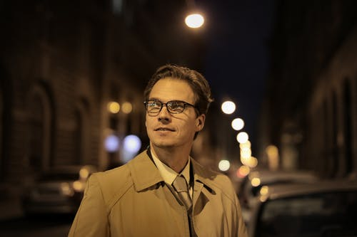 Adult positive well dressed man in eyeglasses standing on city street and looking away