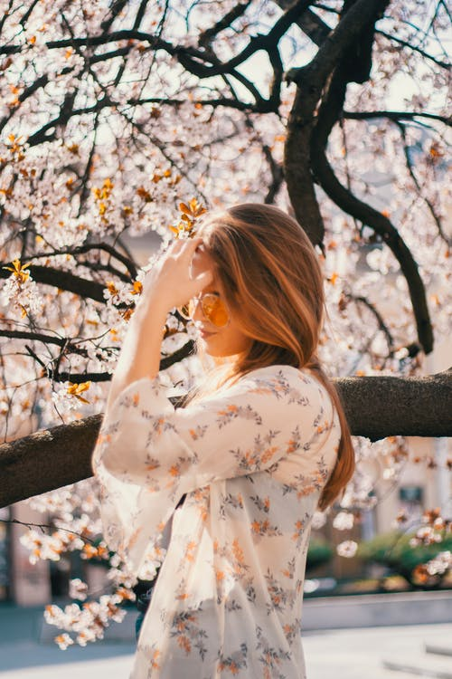 Young woman against blooming tree in garden