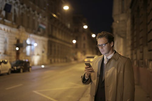 Concentrated adult formally dressed man in glasses surfing internet on cellphone while standing on empty street