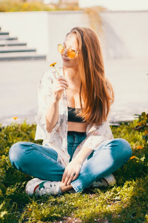 Trendy young woman with bright dandelion sitting on grass