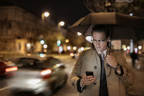 Concentrated man with umbrella using mobile phone