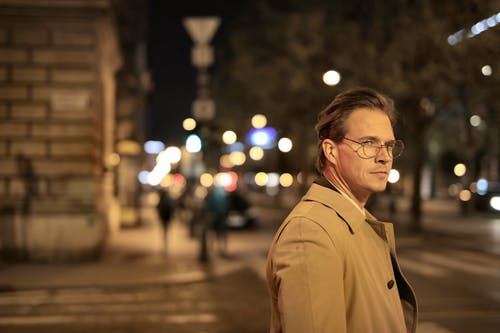 Side view of serious adult male in stylish trench and eyeglasses standing on city street and pensively looking away