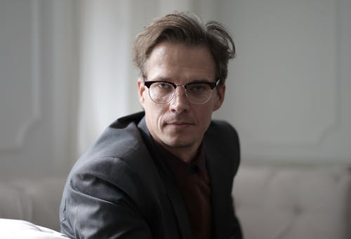 Serious adult man in eyeglasses looking at camera