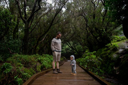 Father with child enjoying dense forest