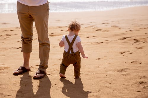 Anonymous dad looking after small kid carefully stepping on sandy beach in sunny day