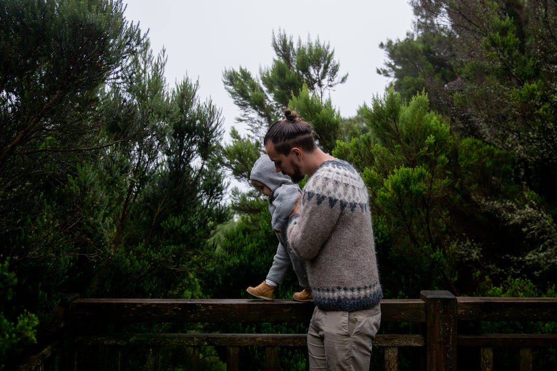 Side view of middle age dad with beard playing with child in green forest