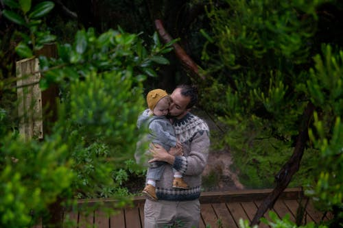 Happy father kissing child in dense forest