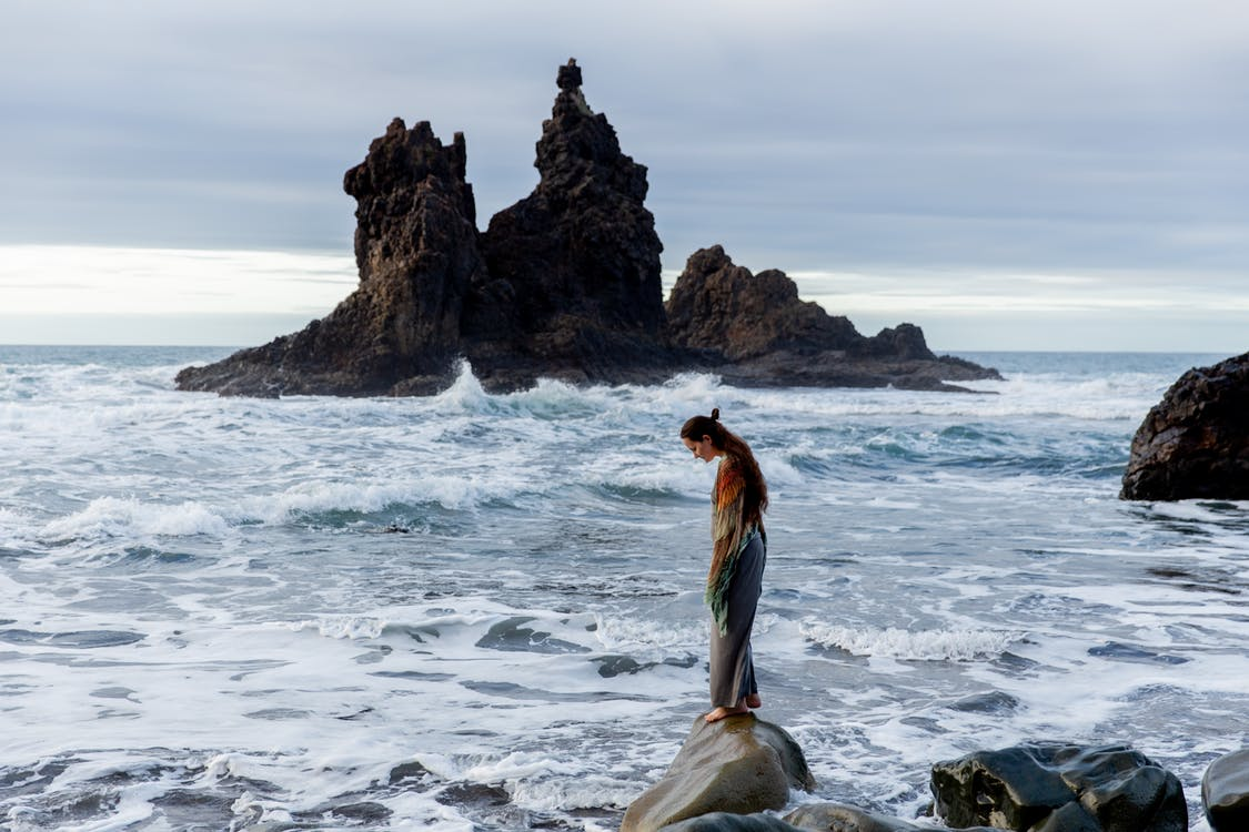 Side view of lonely sad female standing on stone in front of storming ocean