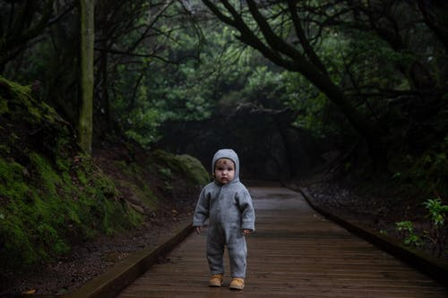 Small kid standing on planked footpath