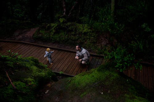 From above of middle age man with happy kid on footpath in dark forest