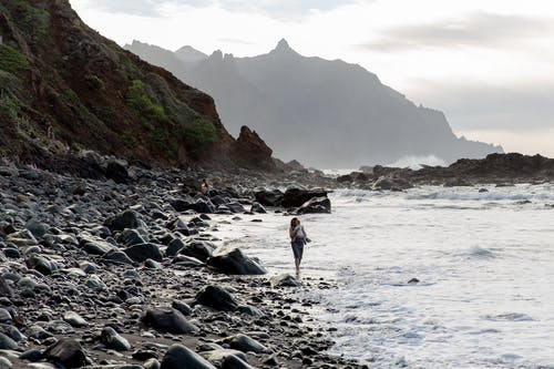 Person Walking on Rocky Shore
