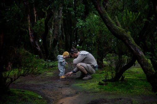 Side view of young man wearing hiking boots and warm sweater during hiking with toddler baby inside coniferous forest covered of green moss while walking on trail