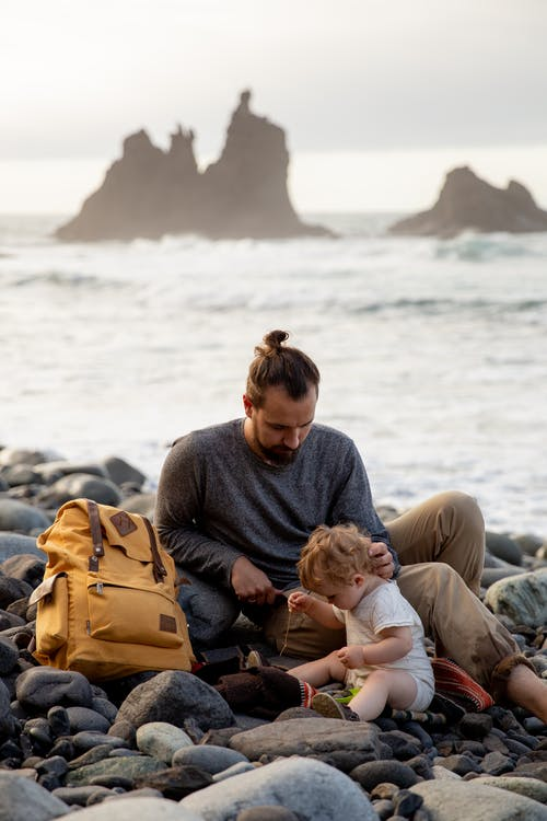 Peaceful young father with adorable little child resting on rocky shore