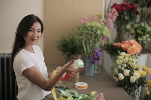Young satisfied female florist working in flower store with colorful bands in rolls near counter with fresh bouquets while smiling and looking at camera