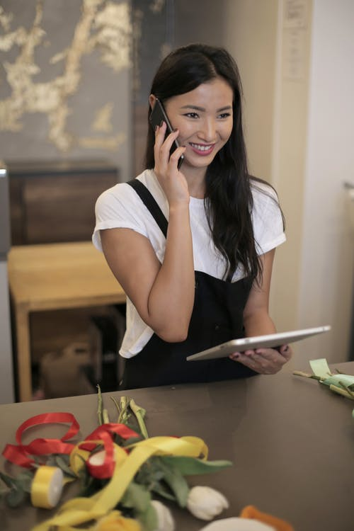 Smiling young Asian female florist wearing apron speaking on smartphone with tablet in hands while receiving new order for flowers delivery service while standing at counter with fresh tulips and silk colorful bands