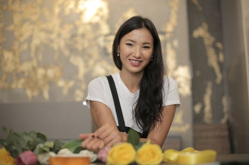 Positive ethnic female florist wearing apron smiling and looking at camera while standing near counter with fresh roses and silk tapes for composing bouquet inside flower store