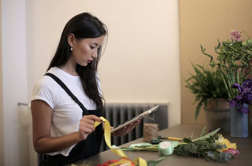 Focused ethnic businesswoman using tablet at own floral shop