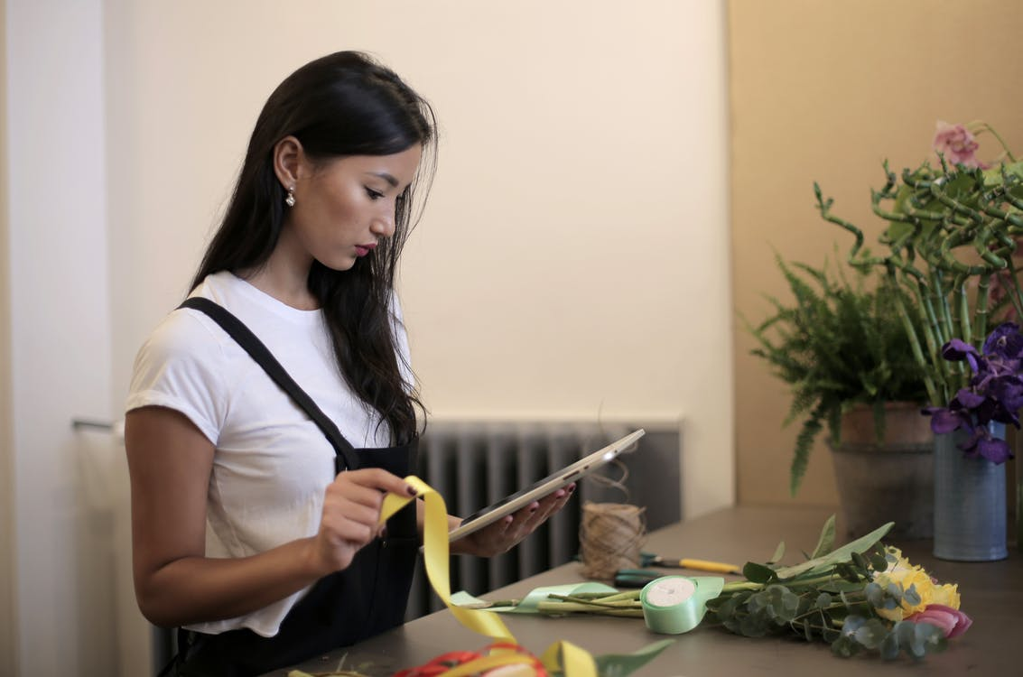 Side view of concentrated young Asian female florist wearing apron checking order on tablet while working with silk band for bouquet decoration in flower store
