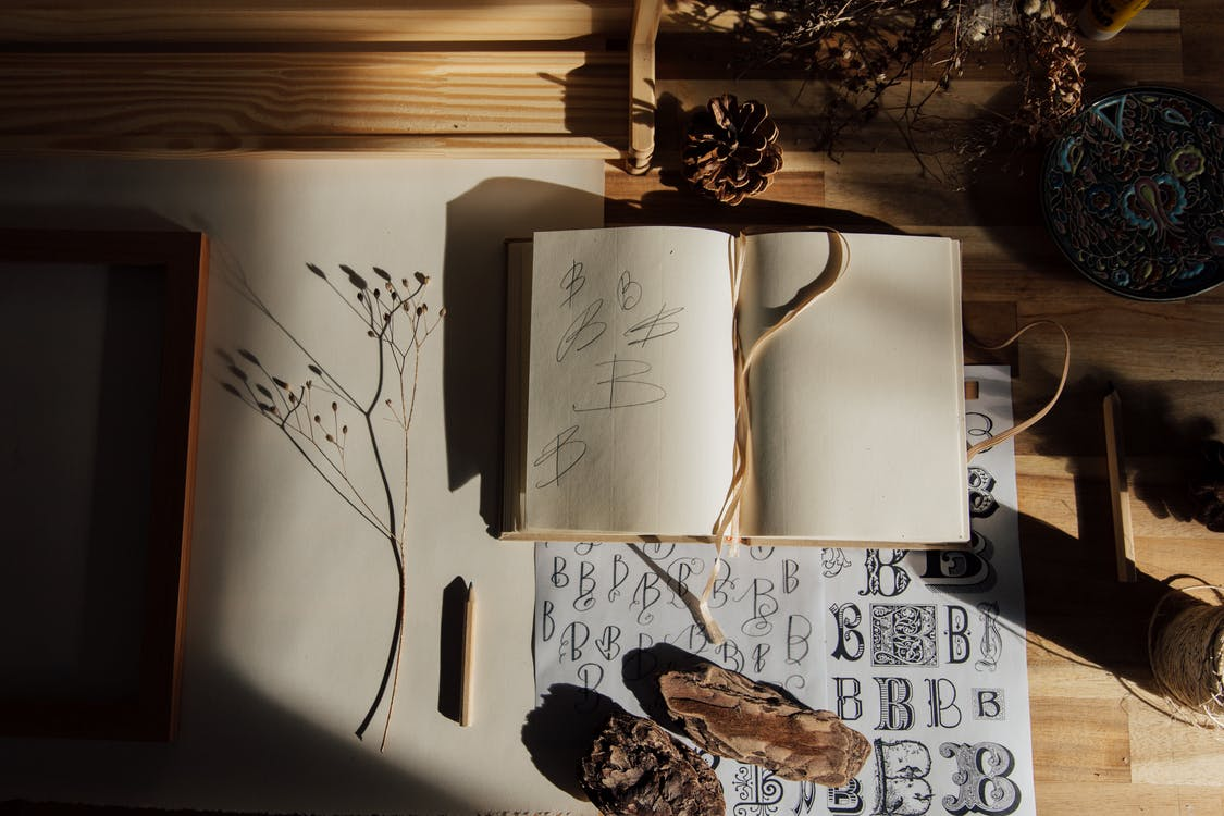 Top view of opened notebook with pencil and dried flower placed on wooden table near other decorative elements illustrating handwriting practice as hobby