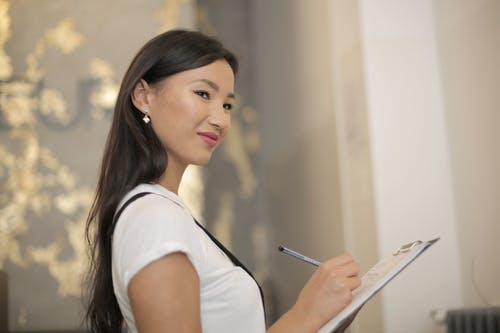 Cheerful young ethnic woman checking list of orders during work in creative studio