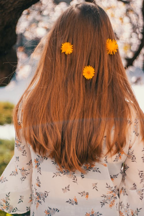 Back view of unrecognizable woman with yellow dandelion in hair standing in bright summer park