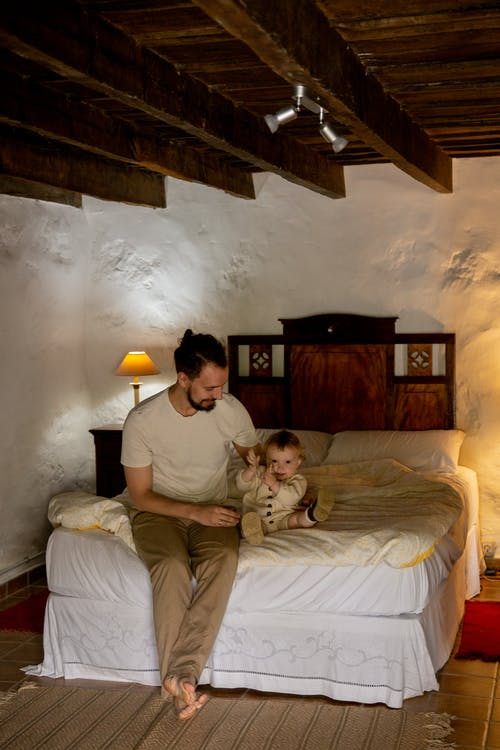 Happy bearded man with toddler sitting on bed in rural interior house