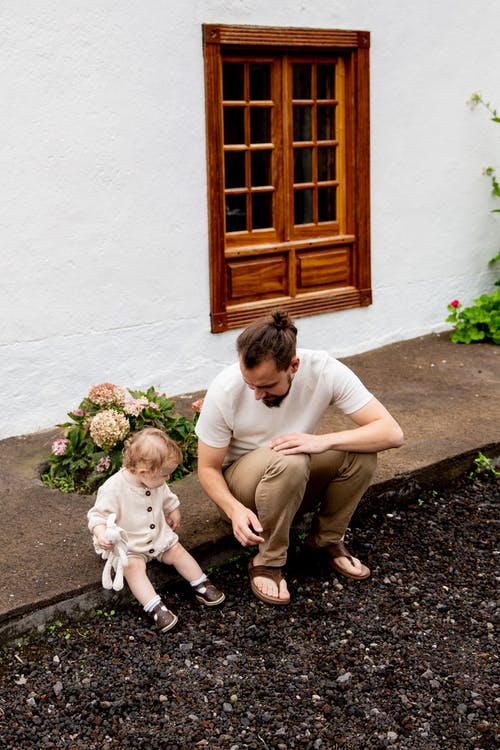 Curious father and daughter playing near rural house